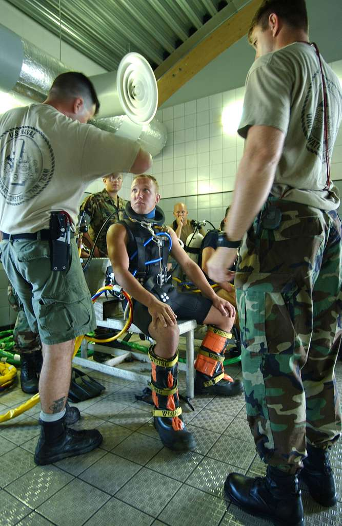 U.S. Navy divers from Little Creek, Va., provide instruction to an Estonian Navy Diver before his familiarization training with underwater emergency procedures on the MK-21 Dive Helmet.