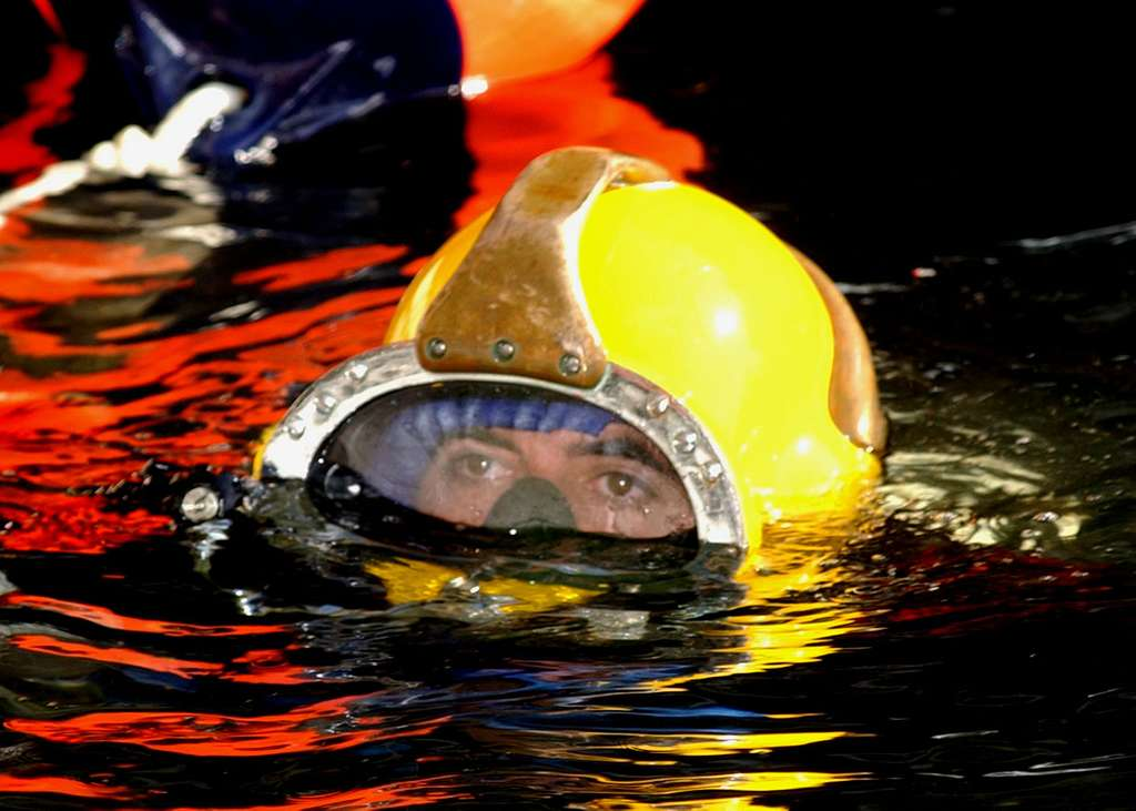 Navy diver, Construction Electricians Mate 2nd Class Rob Soto assigned to Underwater Construction Team One (UCT-1) prepares to leave the surface in the MK-21 Mod 0 deep sea diving helmet to begin work on pile restoration in Newport, R.I.