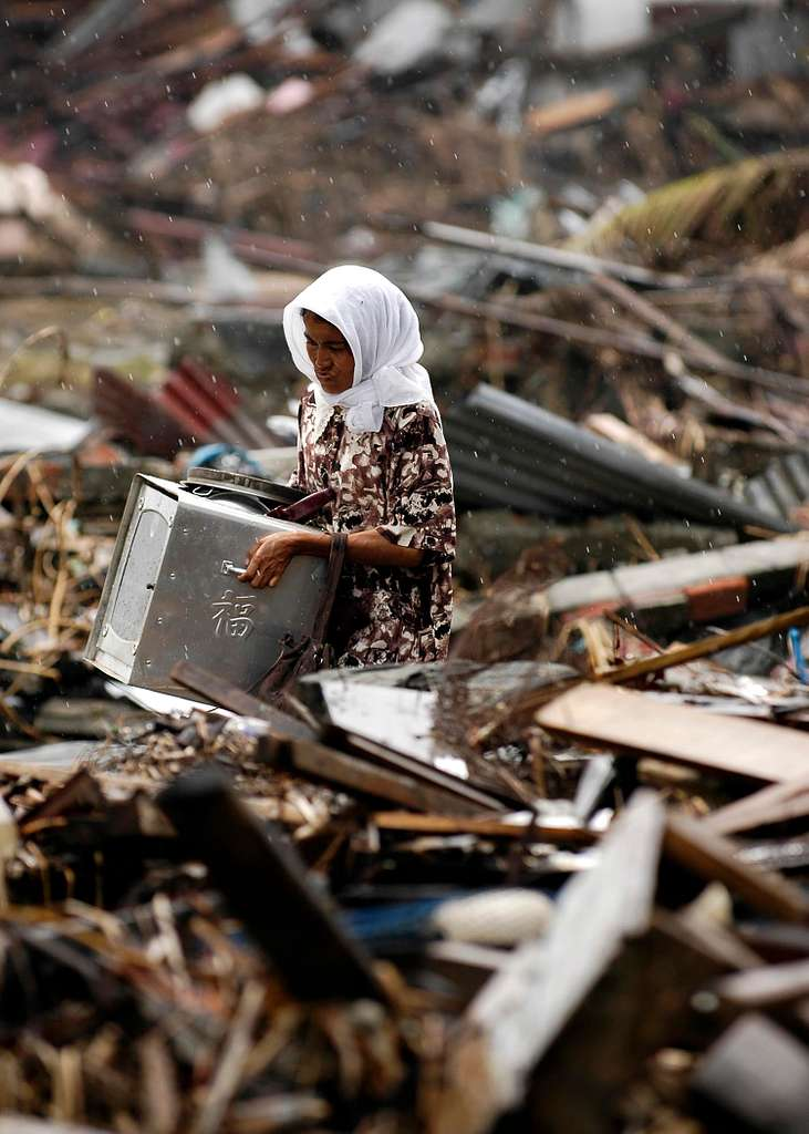 An Indonesian Woman searches through debris in the rain, where her house once stood, in the city of Banda Aceh on the island of Sumatra, Indonesia.