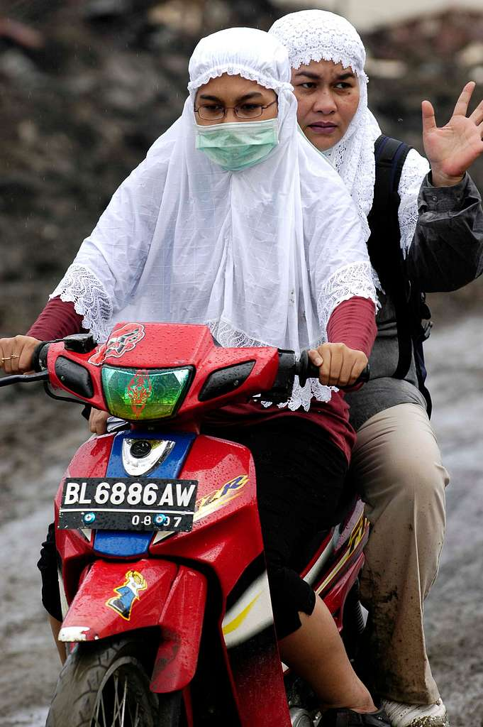 Indonesian Women on a motorcycle ride back from their home that was destroyed due to the Tsunami that struck in Banda Aceh, Sumatra, Indonesia.