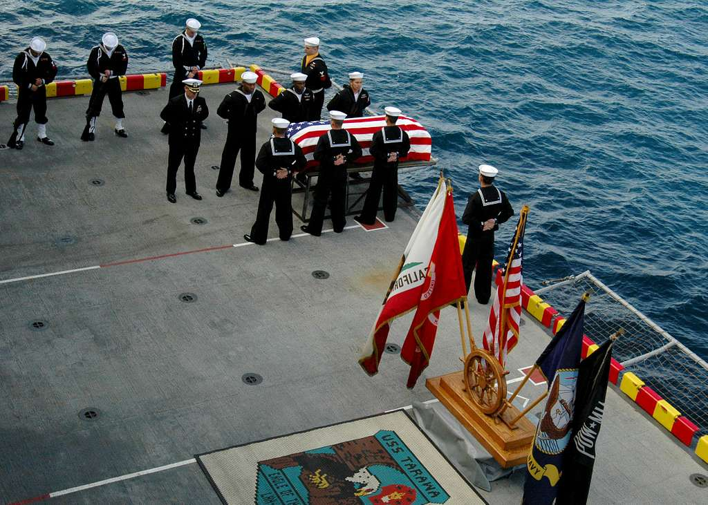 Executive Officer of the USS Tarawa (LHA 1) Capt. Peter D. Murphy and crewmembers stands at parade rest during a burial at sea ceremony.