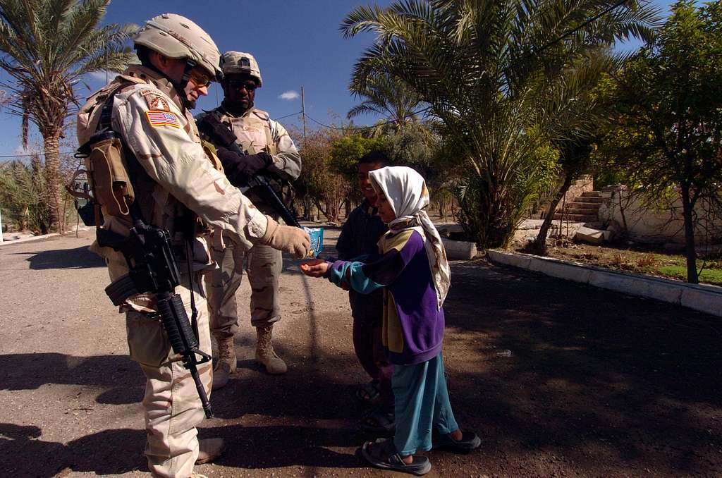 A U.S. Army Solider, assigned to the 256th Brigade Combat Team (BCT), 2nd Battalion, hands-out trail mix to local children while delivering fertilizer to local farmers near Baghdad, Iraq.