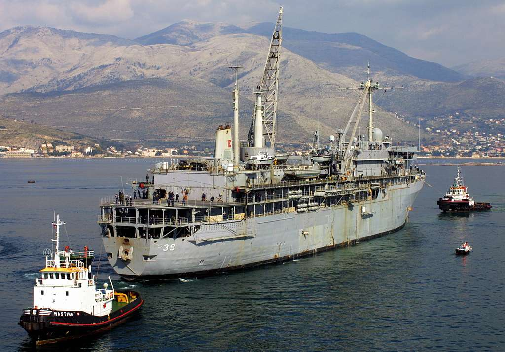 Tugboats, help maneuver the submarine tender, USS Emory S. Land (AS 39), alongside the command ship, USS La Salle (AGF 3), in preparation for a scheduled availability period.