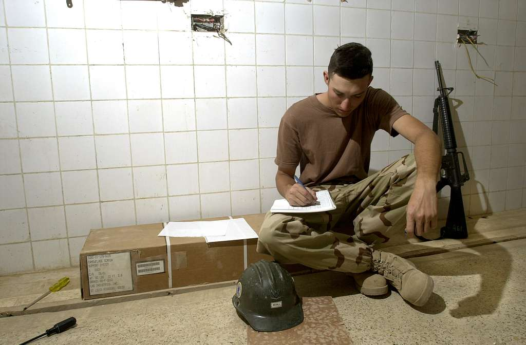 Builder 3rd Class Brian Beall examines paper work for Naval Mobile Construction Battalions Seventy Four (NMCB-74) newly constructed supply spaces.
