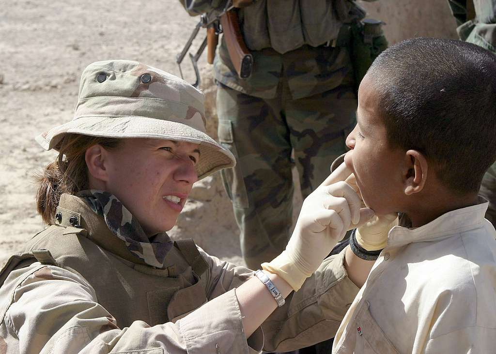 U.S. Navy Lt. Amy Plant, a Navy dentist, examines the teeth and gums of a young Afghan boy during a Coalition medical/dental civil affairs project in the village of Najoy, Afghanistan.