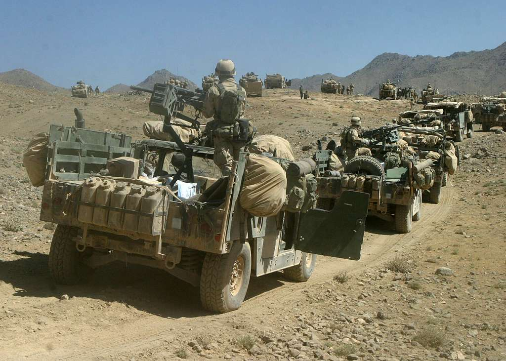 U.S. Marines assigned to Battalion Landing Team 1st Bn., 6th Marines wait for the word to move toward a mountain.