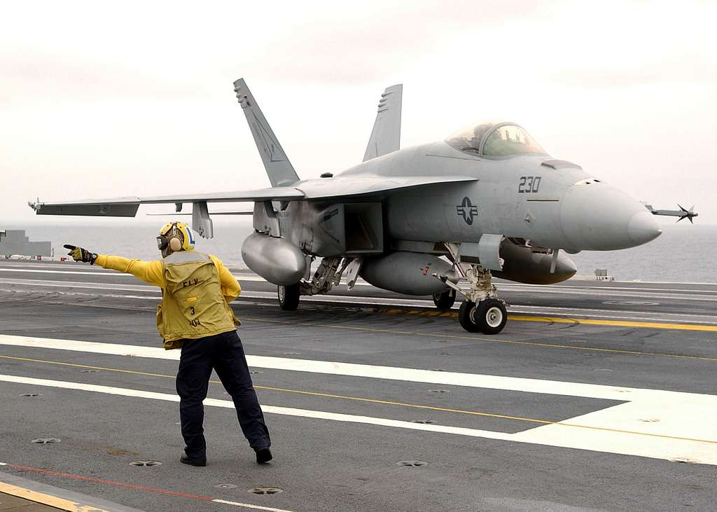 Aviation Boatswain�s Mate Airman Vince Pascua, of San Diego, gives directions to a F/A-18E Hornet .