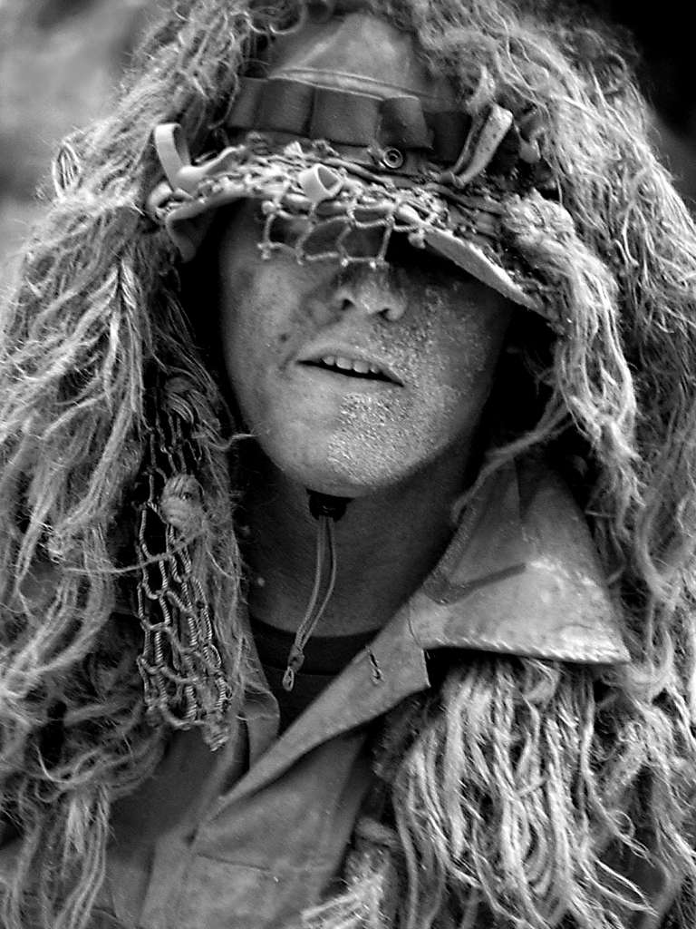 A U.S. Navy SEAL (Sea, Air, Land) conceals himself under camouflage during a demonstration of seizing a beach.