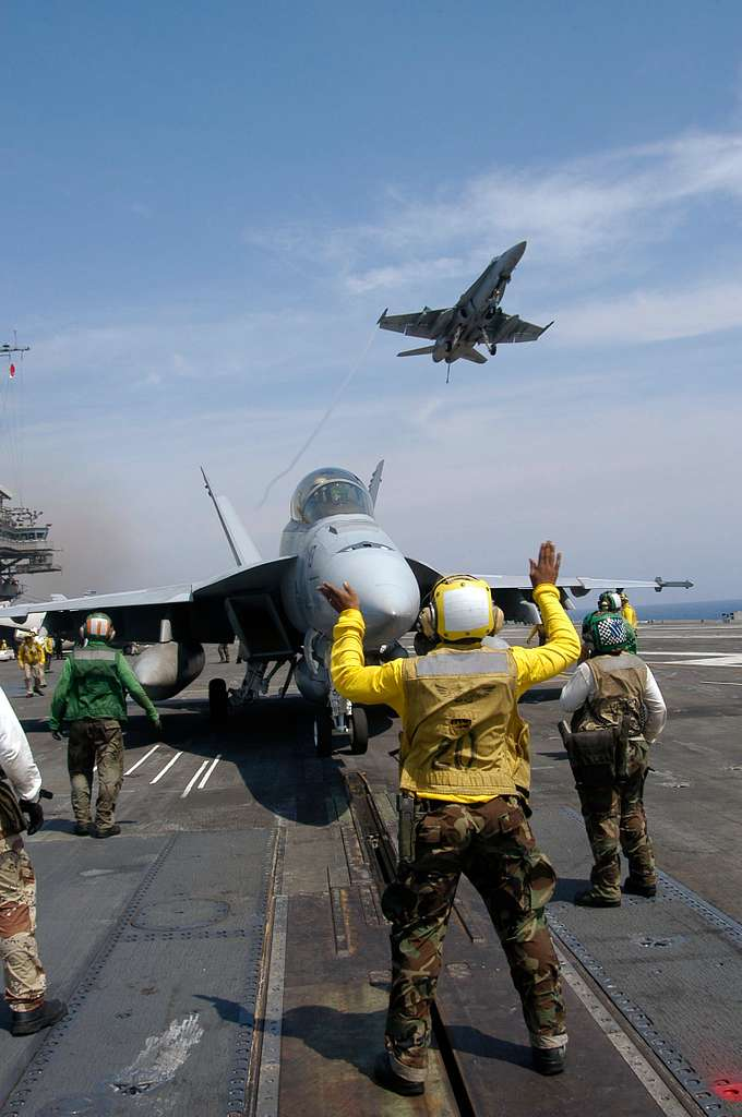 Aviation Boatswain's Mate 3rd Class Marion Roper from Grove Hill, Ala., directs an F/A-18F Super Hornet into position to be launched from the flight deck of USS Kitty Hawk (CV 63).
