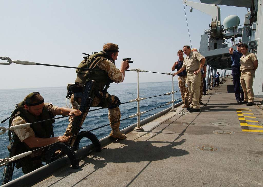 Commander, Destroyer Squadron Two Four (COMDESRON 24), Capt. Anthony Kurta and Lt. Shane Crockett, observe the boarding procedures demonstrated by the British Royal Marines aboard the frigate HMS Somerset (F 82).