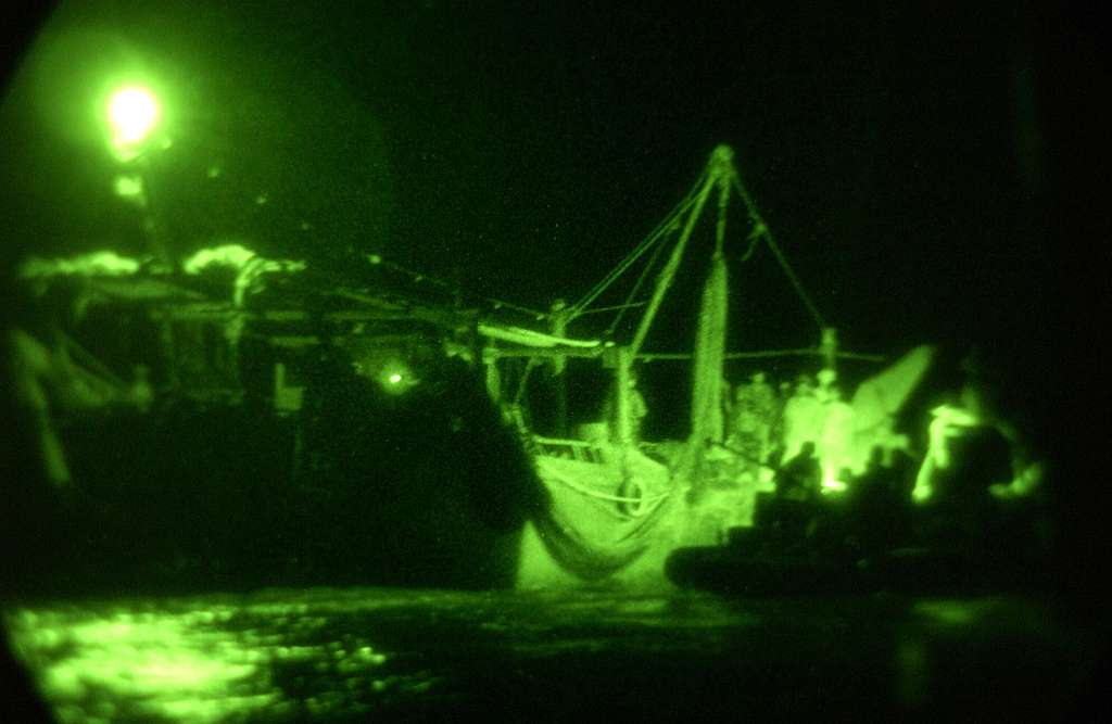 U.S. Navy special forces and Marines prepare to board a dhow from two 11-meter Rigid Hull Inflatable Boats (RHIB) during nighttime Maritime Interception Operations (MIO).