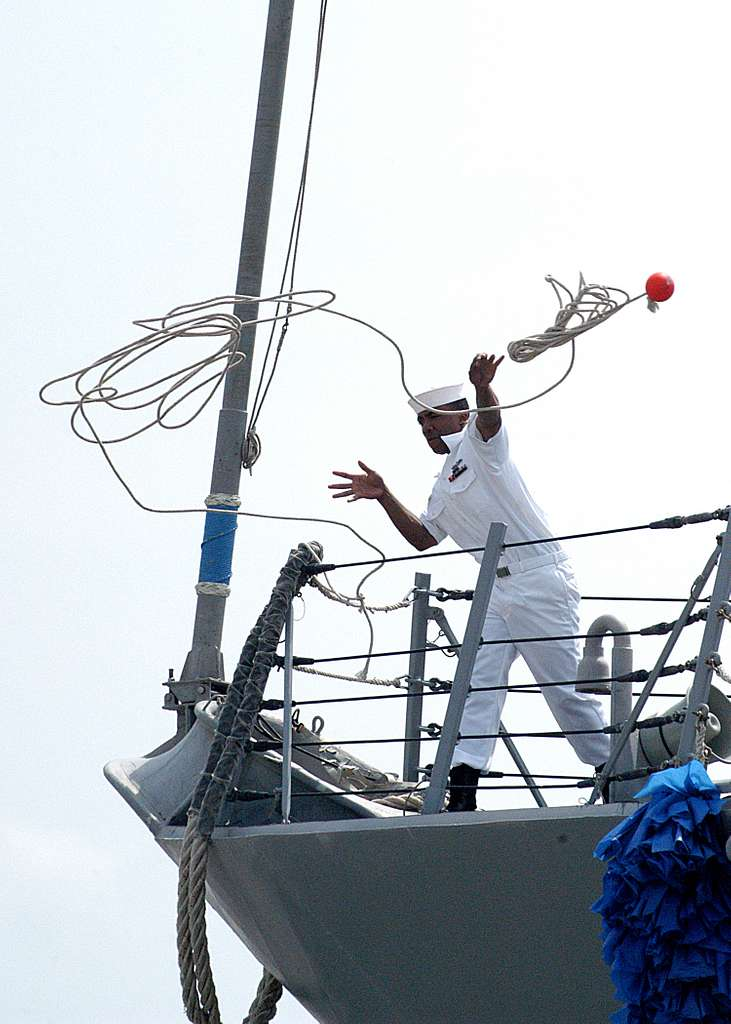 A Sailor assigned to the guided missile destroyer USS Ross (DDG 71) throws a line to the pier.