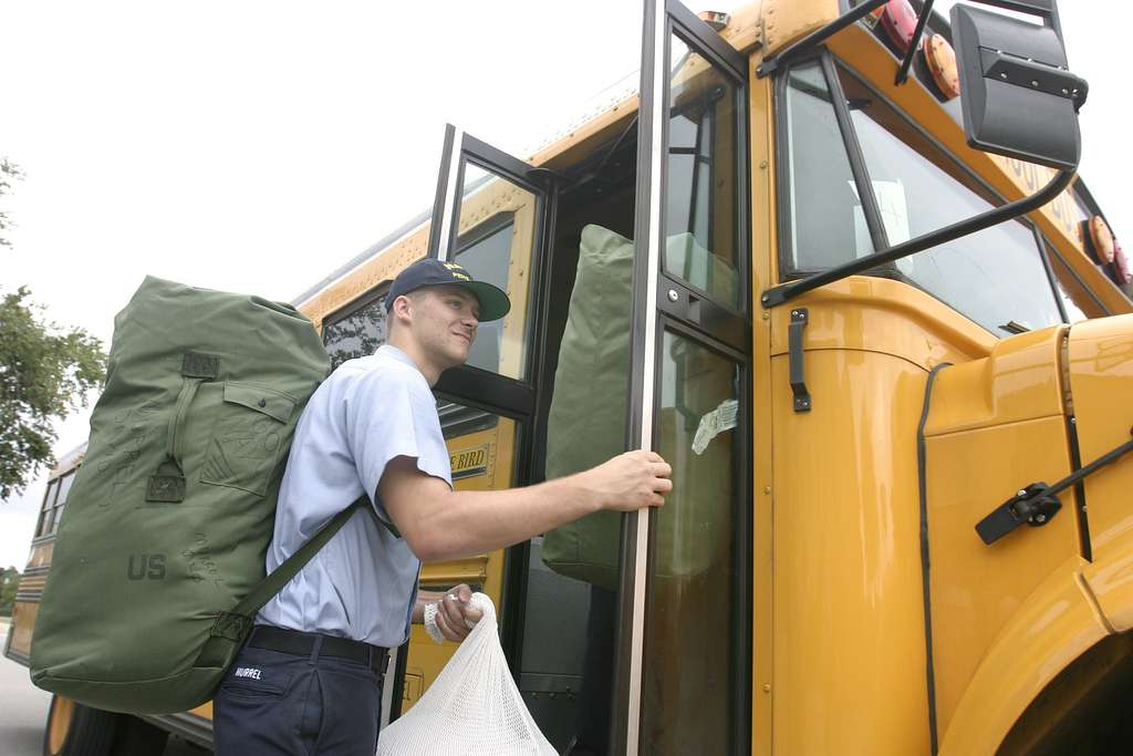 Airman David Murrel, assigned to Naval Aviation Technical Training Center (NATTC), boards an Escambia County school bus as they evacuate Naval Air Station Pensacola.