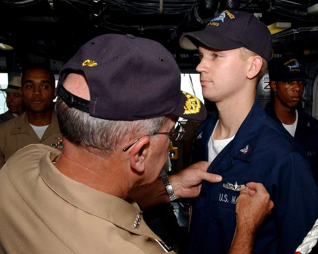 Chief of Naval Operations, Adm. Vern Clark, pins a Surface Warfare pin on a 3rd Class Petty Officer during a ceremony aboard the destroyer USS Spruance (DD 963).