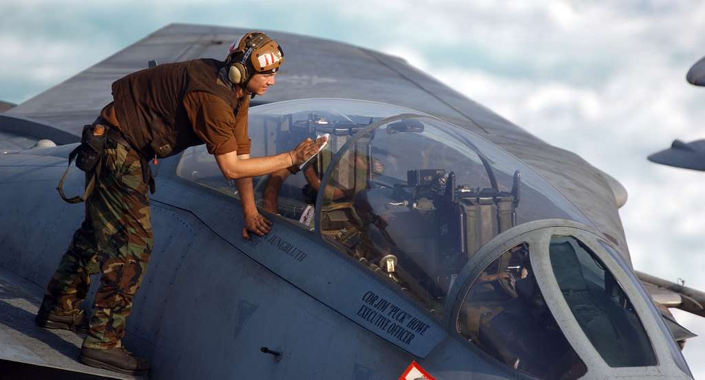 A plane captain cleans the canopy of an F-14D Tomcat, assigned to the Tomcatters of Fighter Squadron Three One (VF-31).