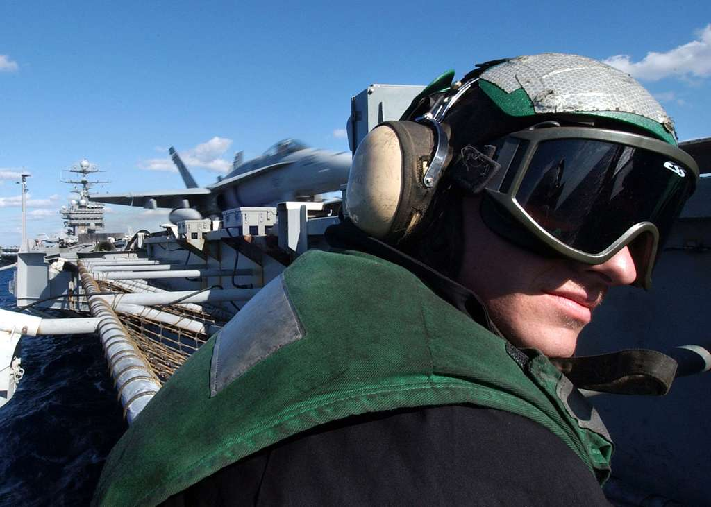 Airman Jason Rodgers, assigned to the V-2 Division, looks away as an F/A-18C Hornet assigned to the Marine Fighter Attack Squadron One One Five (VMFA-115), is launched from the flight deck of USS Harry S. Truman (CVN 75).