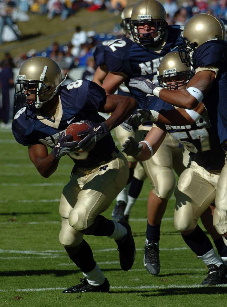 U.S. Naval Academy slotback Jeremy McGown rushes for yardage in the first quarter against the Rice Owls.