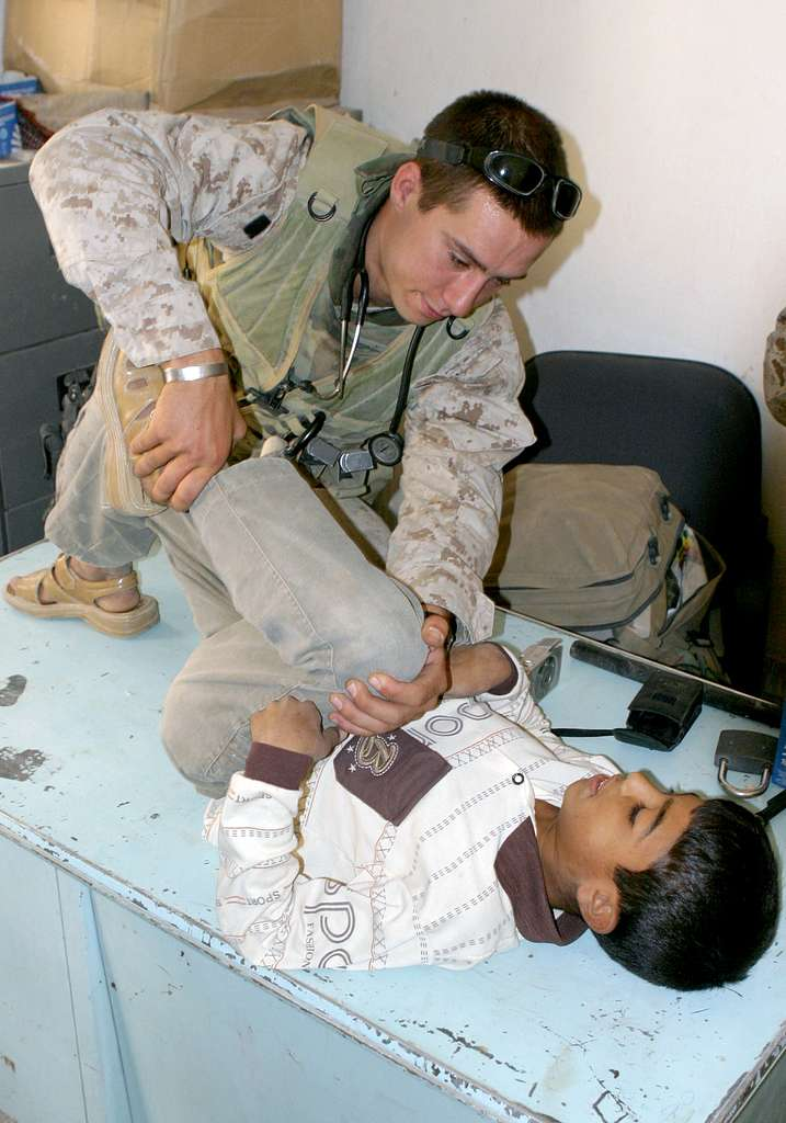 Hospital Corpsmen 3rd Class Nathan Silvers, assigned to the 24th Marine Expeditionary Unit (MEU), bends an Iraqi student�s leg during an evaluation of the boy�s stomach pain.