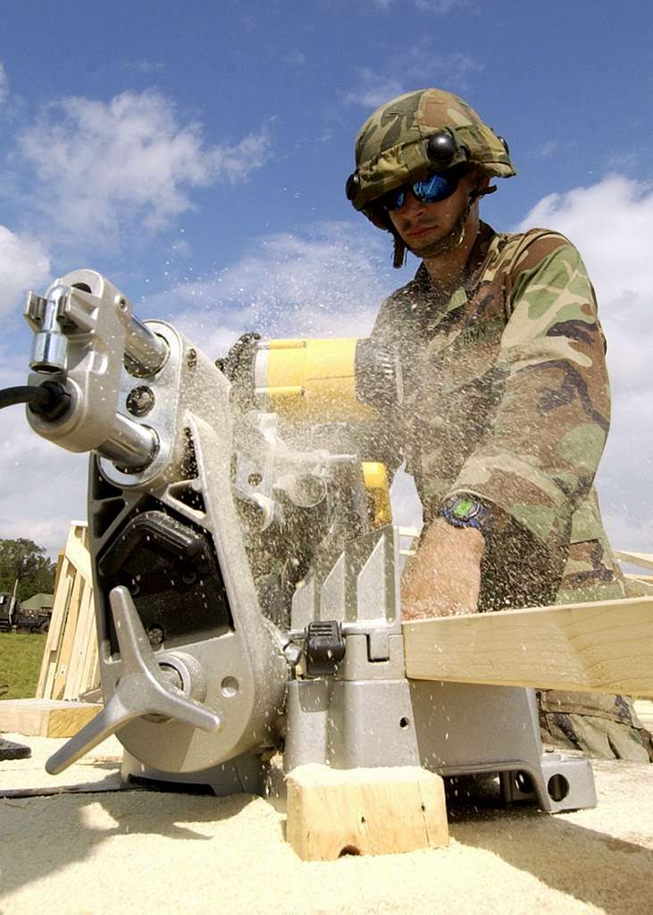 A Seabee assigned to Naval Mobile Construction Battalion One (NMCB-1), cuts 2x4's to make a tent frame for a command and control headquarters during field exercise Operation Gulf Mist at Camp Shelby.