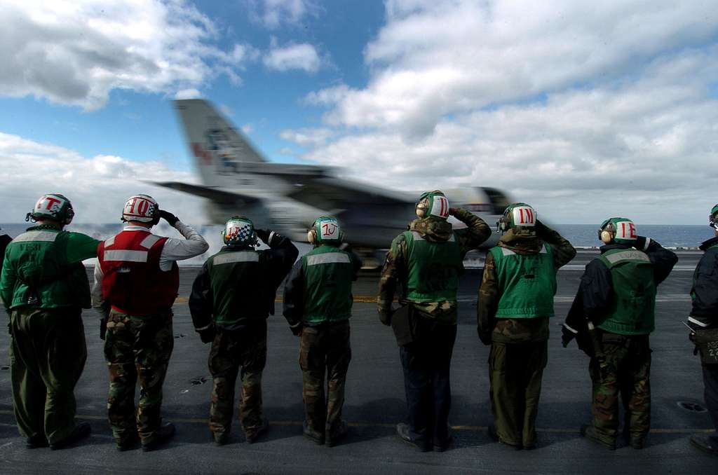 Flight deck personnel salute as the final S-3B Viking assigned to the Blue Wolves of Sea Control Squadron Three Five (VS-35) launches from the Nimitz-class aircraft carrier USS John C. Stennis (CVN 74).