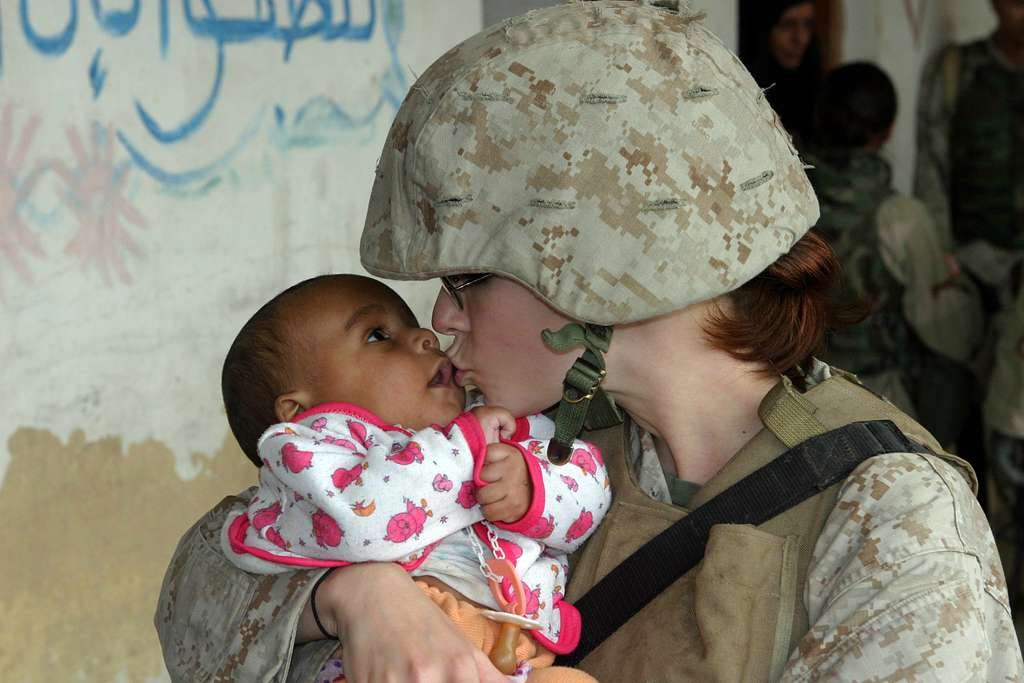 Lance Cpl. Brandy L. Guerrero gives a kiss to an Iraqi baby waiting to be examined during a Humanitarian Assistance Operation (HAO) in the village of Ash Shafiyah, Iraq.