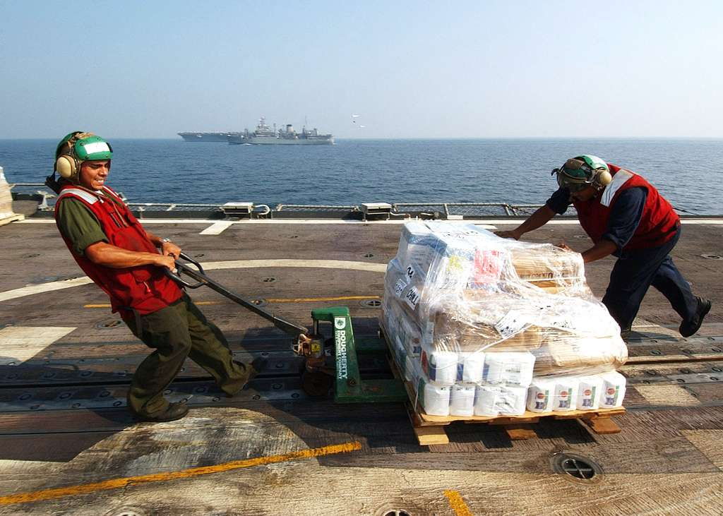 Sailors assigned to the Proud Warriors of Helicopter Anti-Submarine Squadron Light Four Two (HSL-42), move a pallet of stores across the flight deck of the guided missile cruiser USS Vicksburg (CG 69).