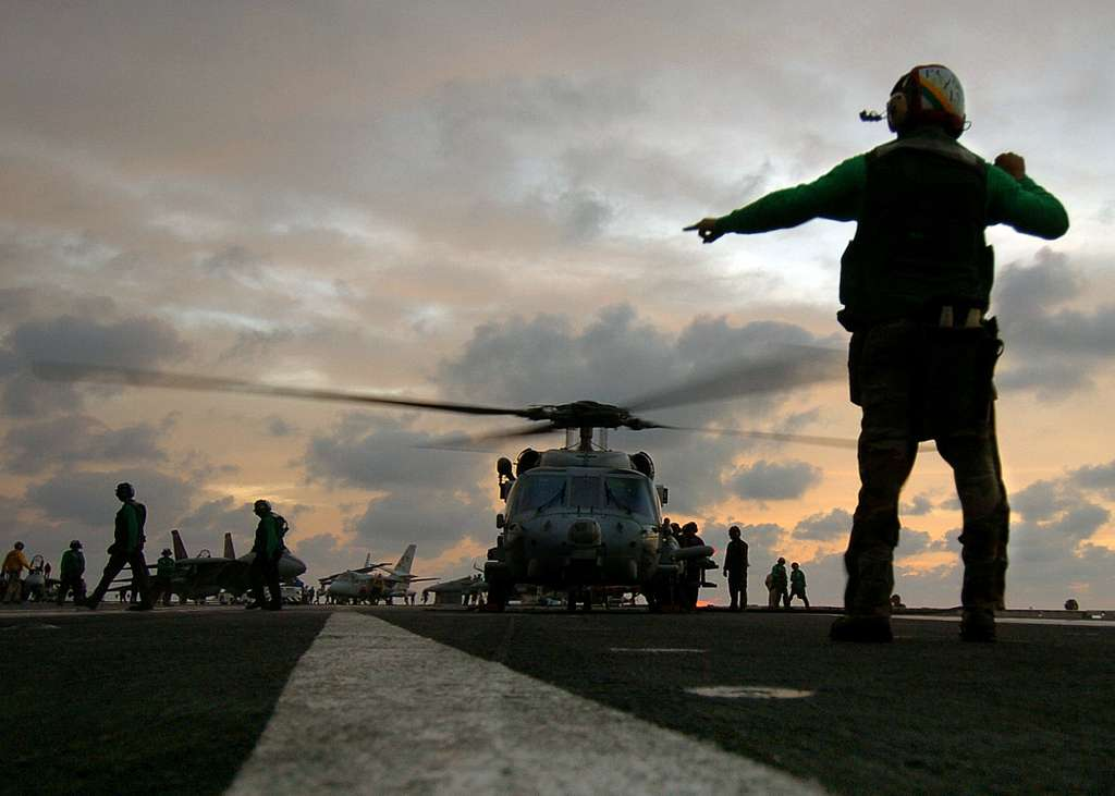 Aviation Electrician's Mate Airman John Broughton signals shipmates to clear the deck as an HH-60H Seahawk helicopter prepares to take off.