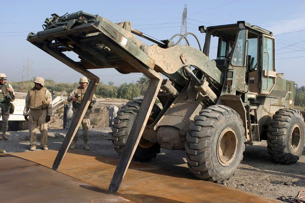 A Seabee assigned to Naval Mobile Construction Battalion Four (NMCB-4), Kalsu Detachment, operates a fork life as it pushes large pieces of sheet metal over an impact crater.