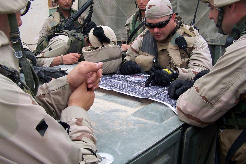 Chief Engineering Aide Ardell Ball, center, assigned to Naval Mobile Construction battalion Four (NMCB-4), studies an aerial photograph of the streets in Fallujah, Iraq.