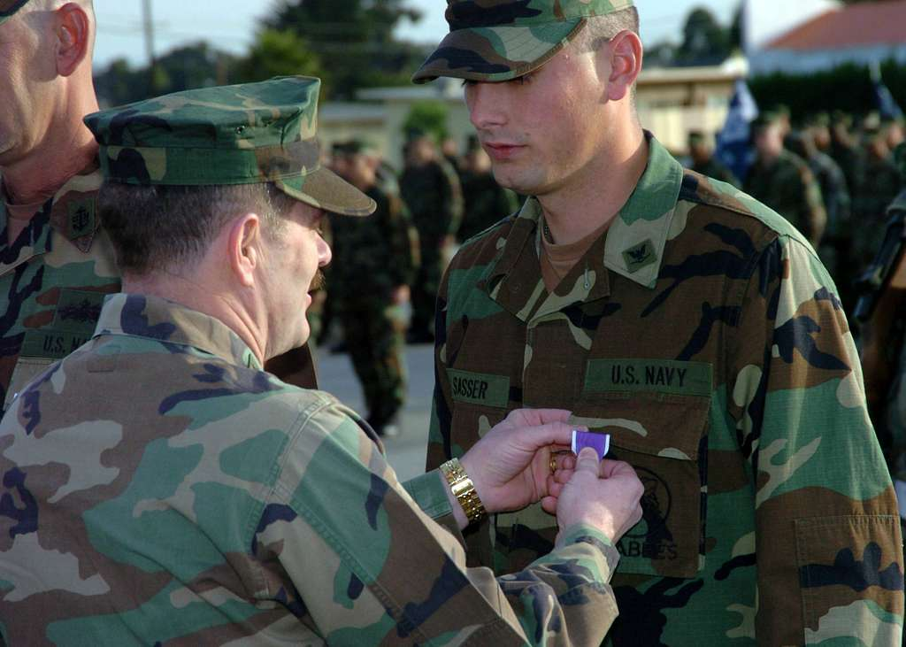 Steelworker 3rd Class Justin Sasser is presented the Purple Heart by Commander, Naval Facilities Engineering Command and Chief of Civil Engineers, Rear Adm. Michael Loose, for wounds received by indirect fire while working in Camp Fallujah, Iraq.