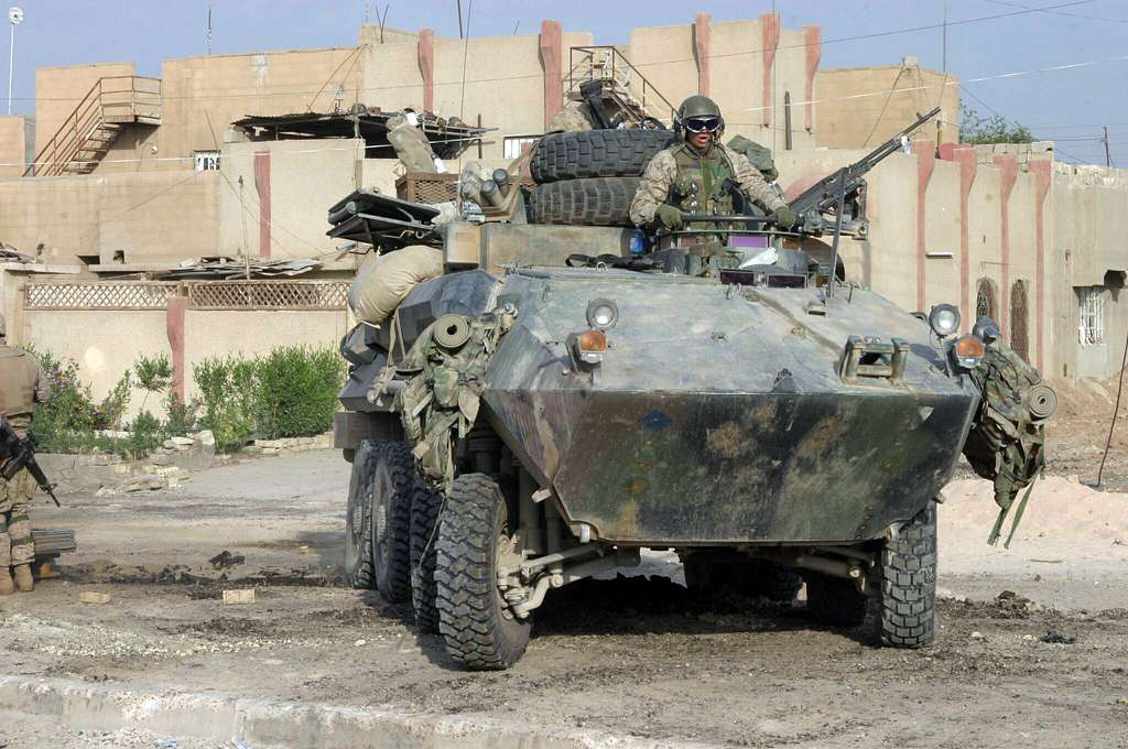 U.S. Marines, assigned to Regimental-sized Combined Arms Team Seven (RCT-7) 1/3 Charlie Company, drive an Assault Amphibian Vehicle (AVV) in the city of Fallujah, Iraq.