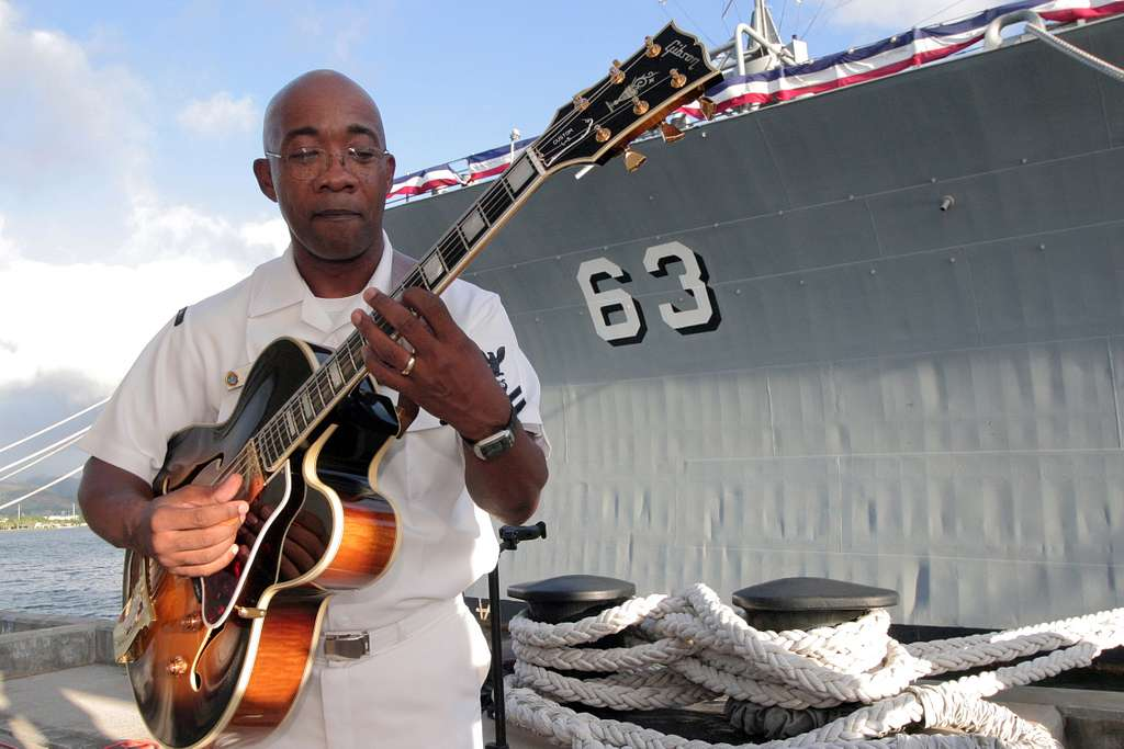 Musician 2nd Class Rufus Spearman, a guitarist in the Pacific Fleet Band, warms up prior to a tribute ceremony.