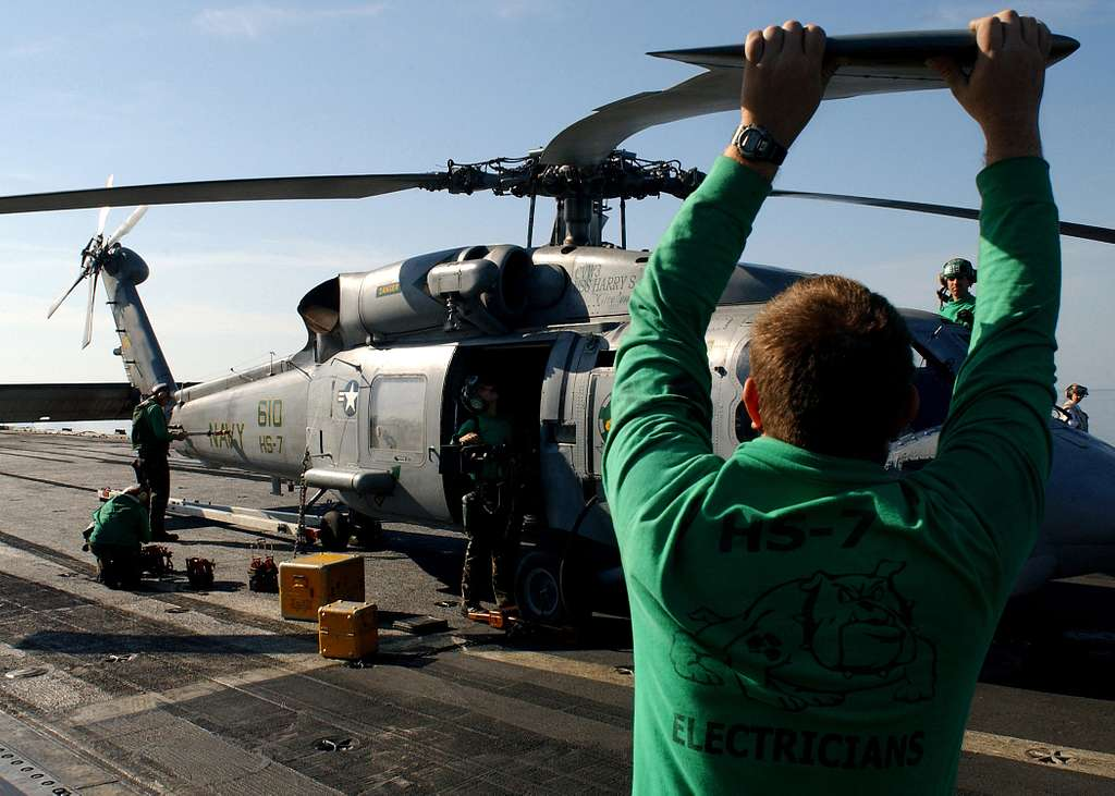 An Aviation Electrician's Mate helps hold the rotors steady while squadron personnel perform routine maintenance on one of the squadron's SH-60F Seahawk helicopters aboard USS Harry S. Truman (CVN 75).