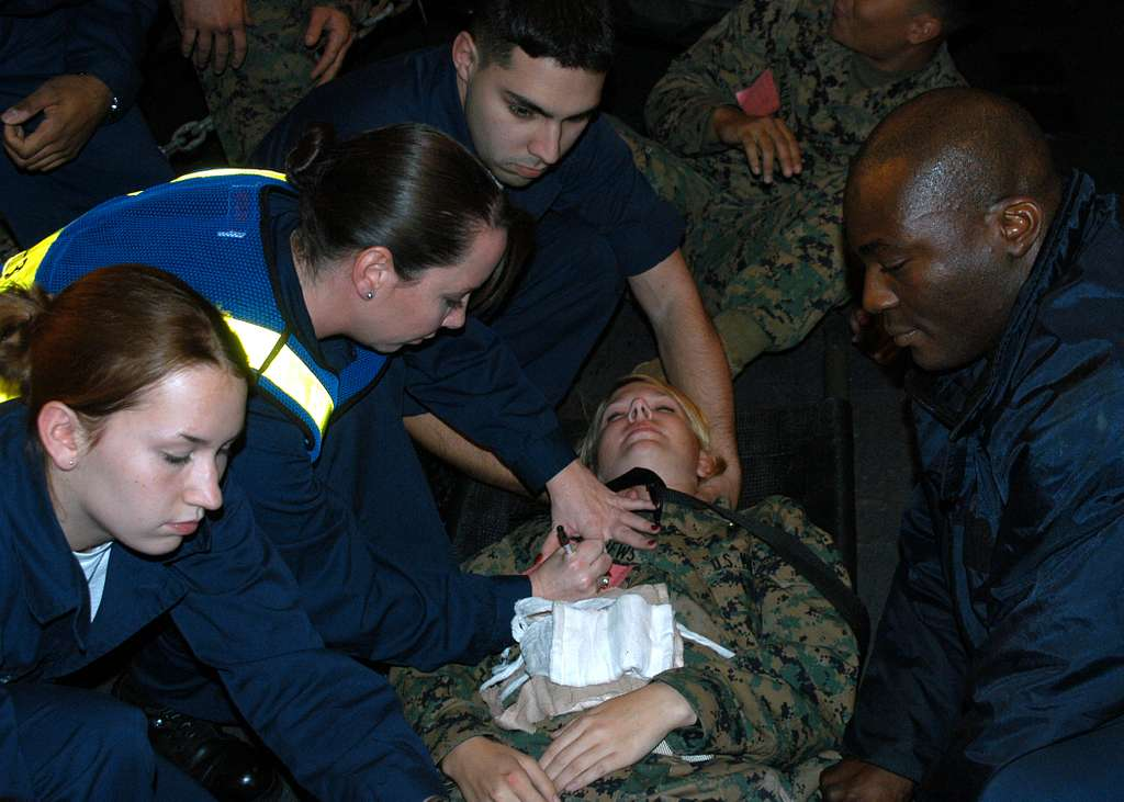 Hospital Corpsman 3rd Class Melody Austin from Ponchatoula, La., second from left, explains to stretcher bearers how to control excess bleeding.