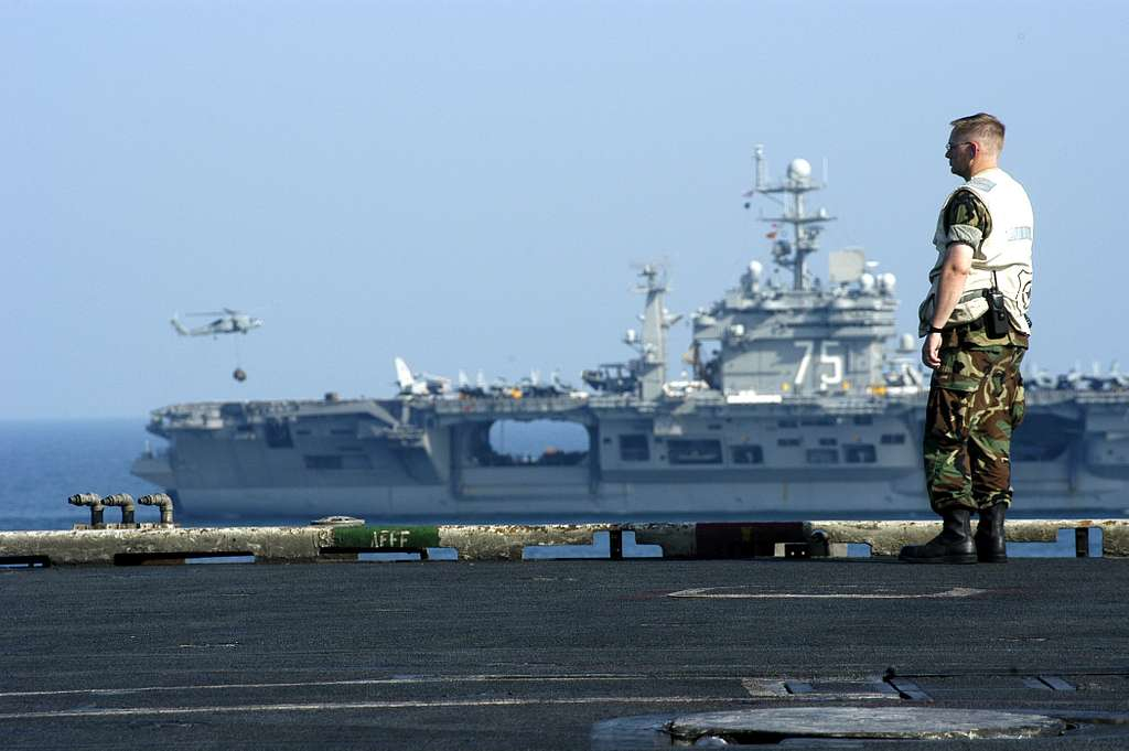 A Master-At-Arms aboard USS John F. Kennedy (CV 67) looks on as USS Harry S. Truman (CVN 75) relieves Kennedy in the Arabian Gulf.