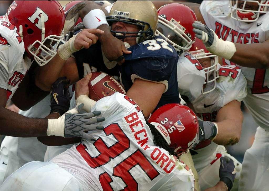 Six Rutgers University defenders attempt to tackle U.S. Naval Academy Midshipman 1st Class Kyle Eckel.