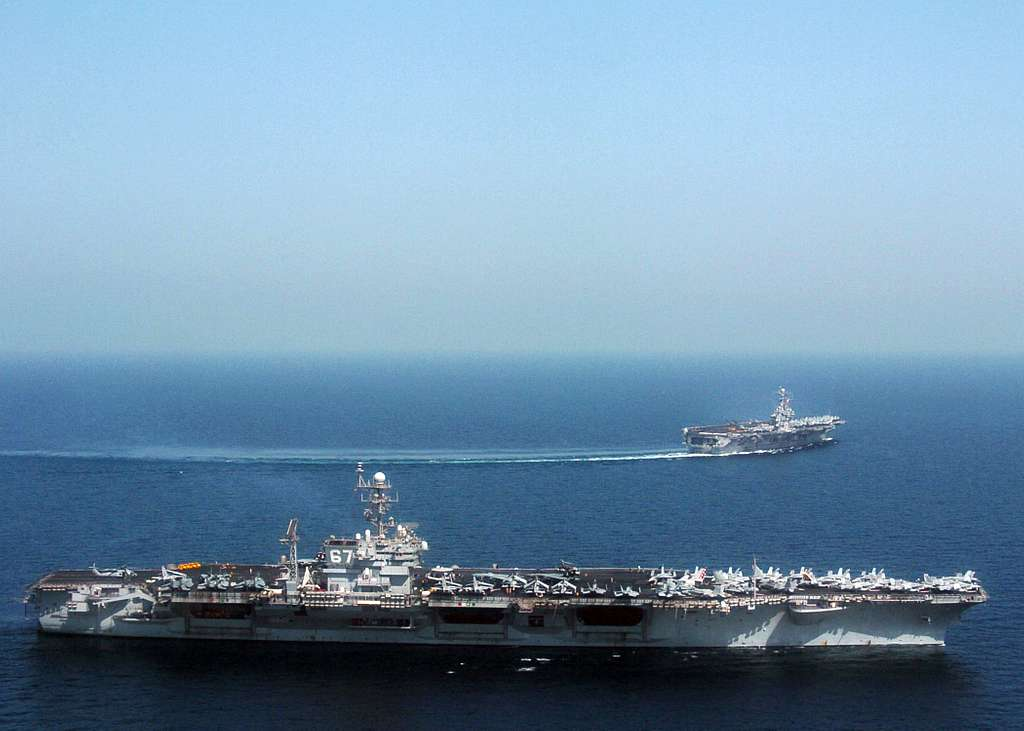 The conventional aircraft carrier USS John F. Kennedy (CV 67), is relieved by the Nimitz-class aircraft carrier USS Harry S. Truman (CVN 75) shown making her turn away from Kennedy, and assuming duties under U.S. Navy Commander Fifth Fleet.