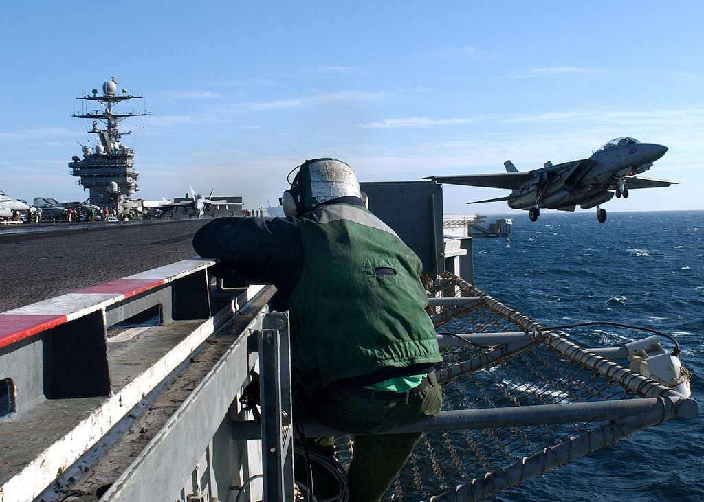 A bow safety watch stander observes an F-14B Tomcat assigned to the Swordsmen of Fighter Squadron Three Two (VF-32), during a launch from the waist catapult aboard the Nimitz-class aircraft carrier USS Harry S. Truman (CVN 75).