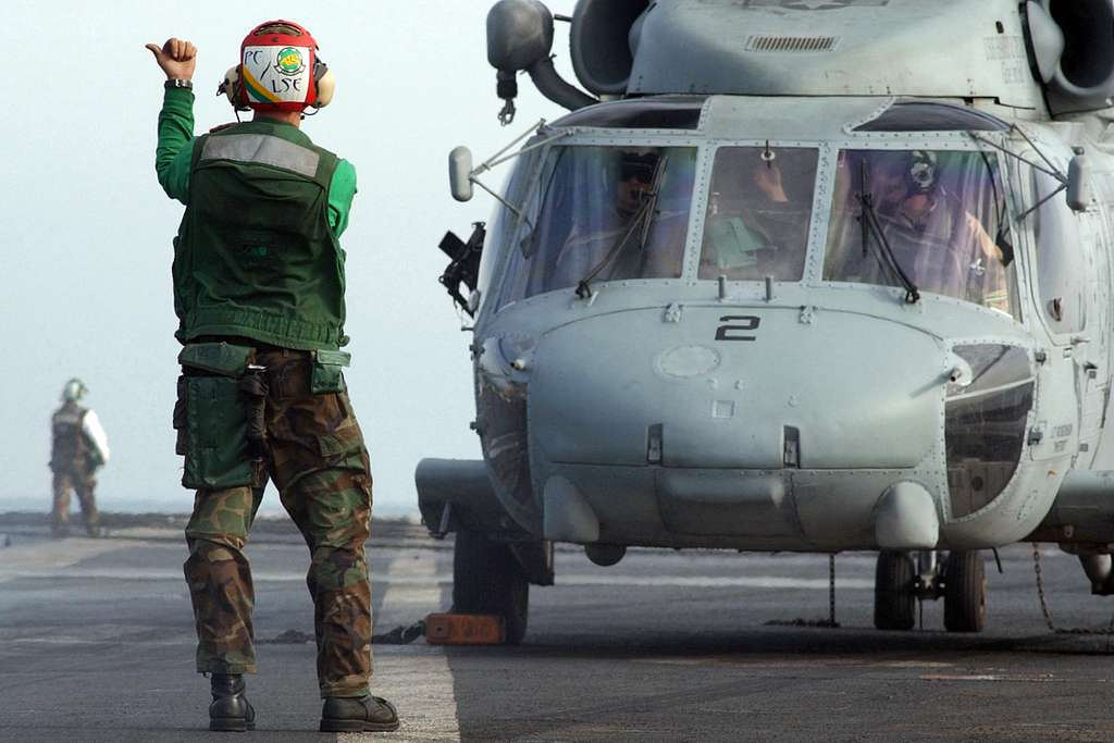 A Landing Signal Enlisted (LSE) directs an SH-60F Seahawk helicopter prior to flight operations aboard the Nimitz-class aircraft carrier USS Harry S. Truman (CVN 75).