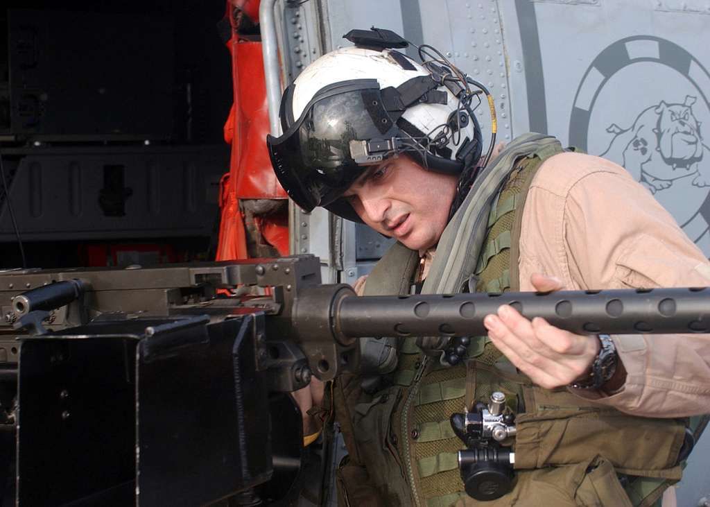 Aviation Warfare Systems Operator 2nd Class Chris Carringer assigned to the Dusty Dogs of Helicopter Anti-Submarine Squadron Seven (HS-7), inspects a .50 caliber machine gun.