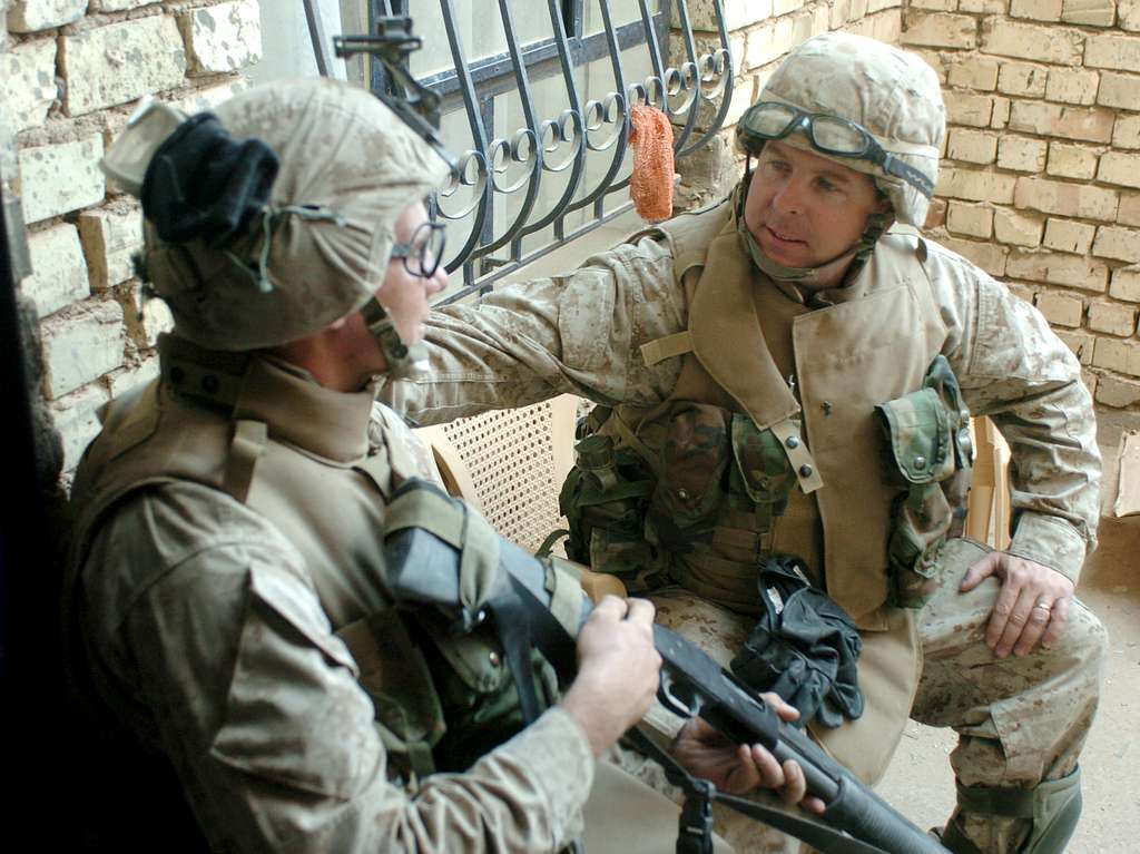 U.S. Navy Chaplain, Lt. Kenny Lee talks with designated marksman, Lance Cpl. Kris Latorre assigned to 3rd Platoon, Charlie Company, 3rd Marine Regiment, during Operation Al Fajr (New Dawn).