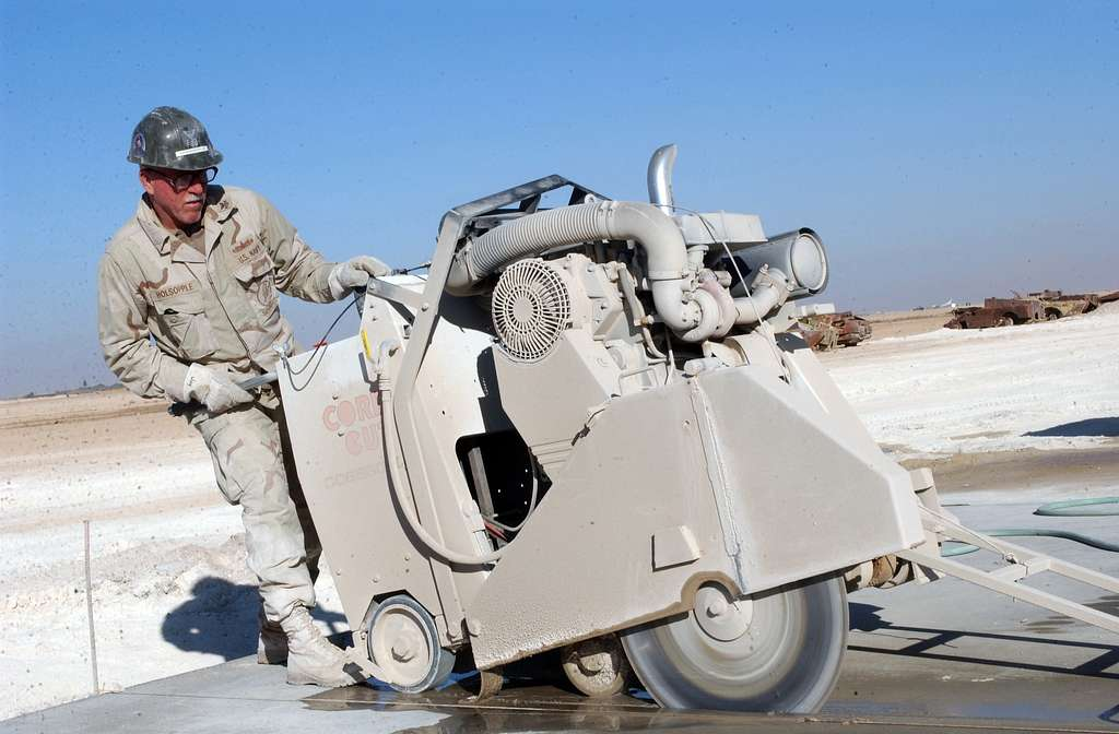 A Navy Seabee assigned to Naval Mobile Construction Battalion Two Three (NMCB-23), cuts a section of cured concrete during repairs to the south runway at Al Asad Airport, Iraq.