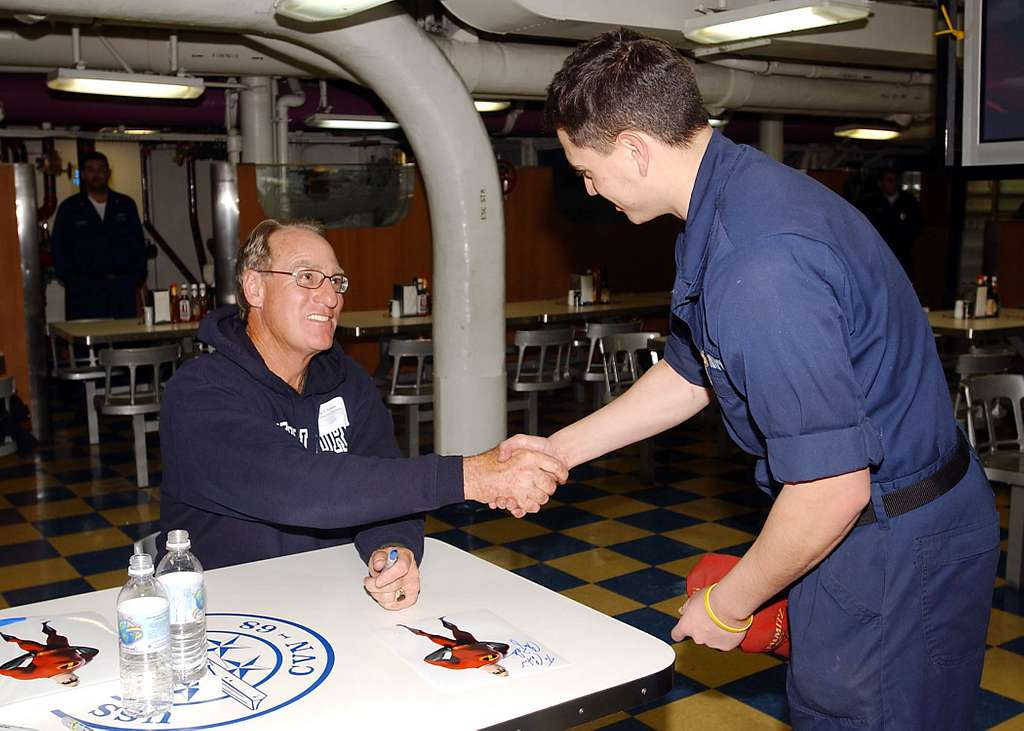 Actor Craig T. Nelson, shakes the hand of Fireman Mike Smith of Beverton, Ore., after signing an autograph in the mess decks aboard the aircraft carrier USS Nimitz (CVN 68).