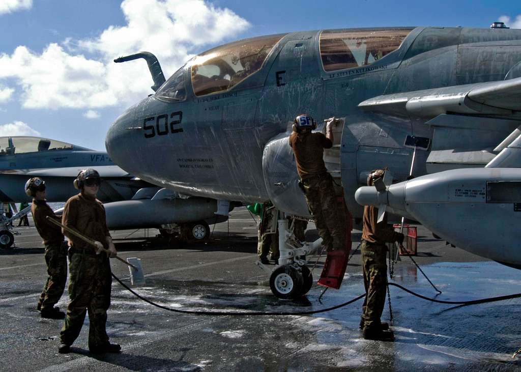 Sailors scrub-down an EA-6B Prowler during a no-fly day on the flight deck aboard the Nimitz-class aircraft carrier USS Abraham Lincoln (CVN 72).
