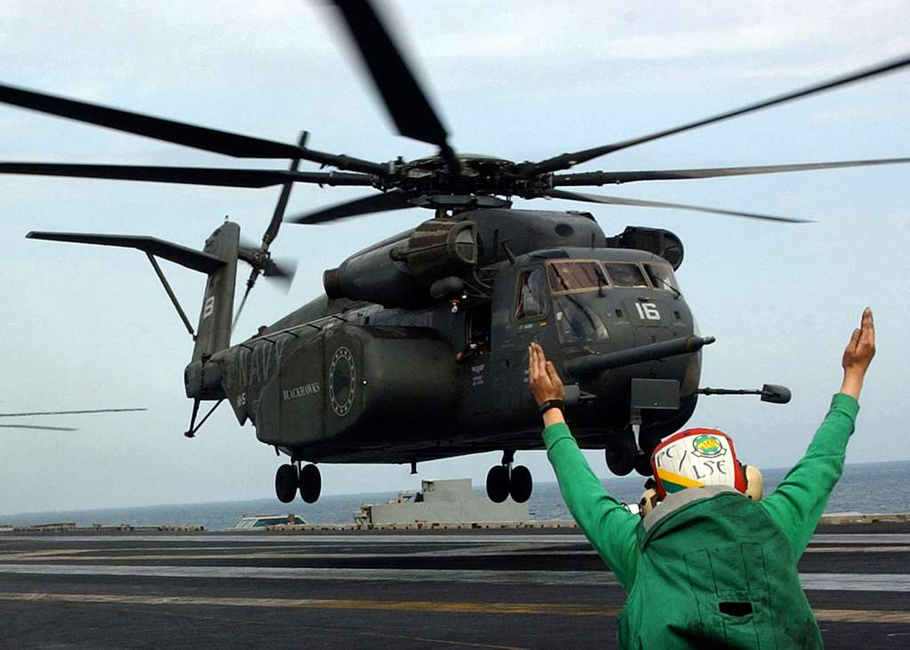 Aviation Electrician's Mate 3rd Class Megan Truncer, assigned to the Dusty Dogs of Helicopter Anti-Submarine Squadron Seven (HS-7) gives the signal to an MH-53E Sea Dragon.