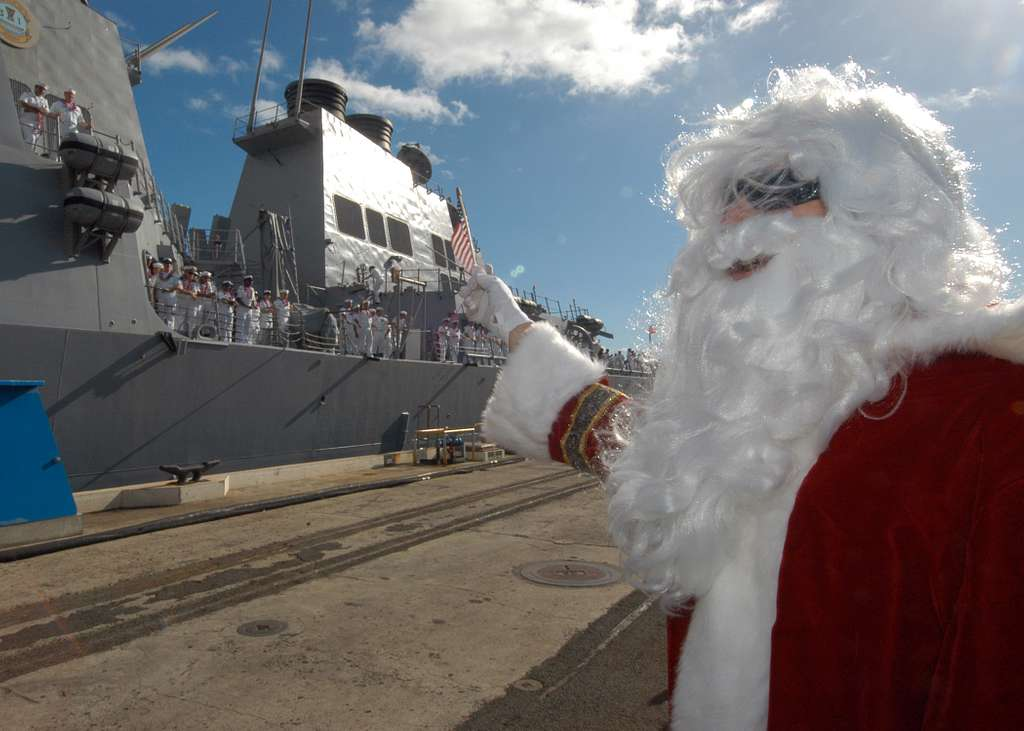 A family member dressed in a Santa Claus costume waves an American flag as the Arleigh Burke-class guided missile destroyer USS Hopper (DDG 70) returns to Pearl Harbor, Hawaii.