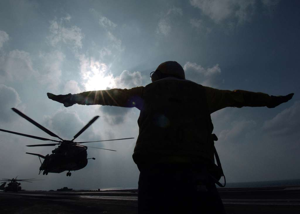 Aviation Boatswain's Mate 2nd Class Christopher Carter signals an MH-53E Sea Dragon that it's clear to lift from the flight deck aboard the Nimitz-class aircraft carrier USS Harry S. Truman (CVN 75).