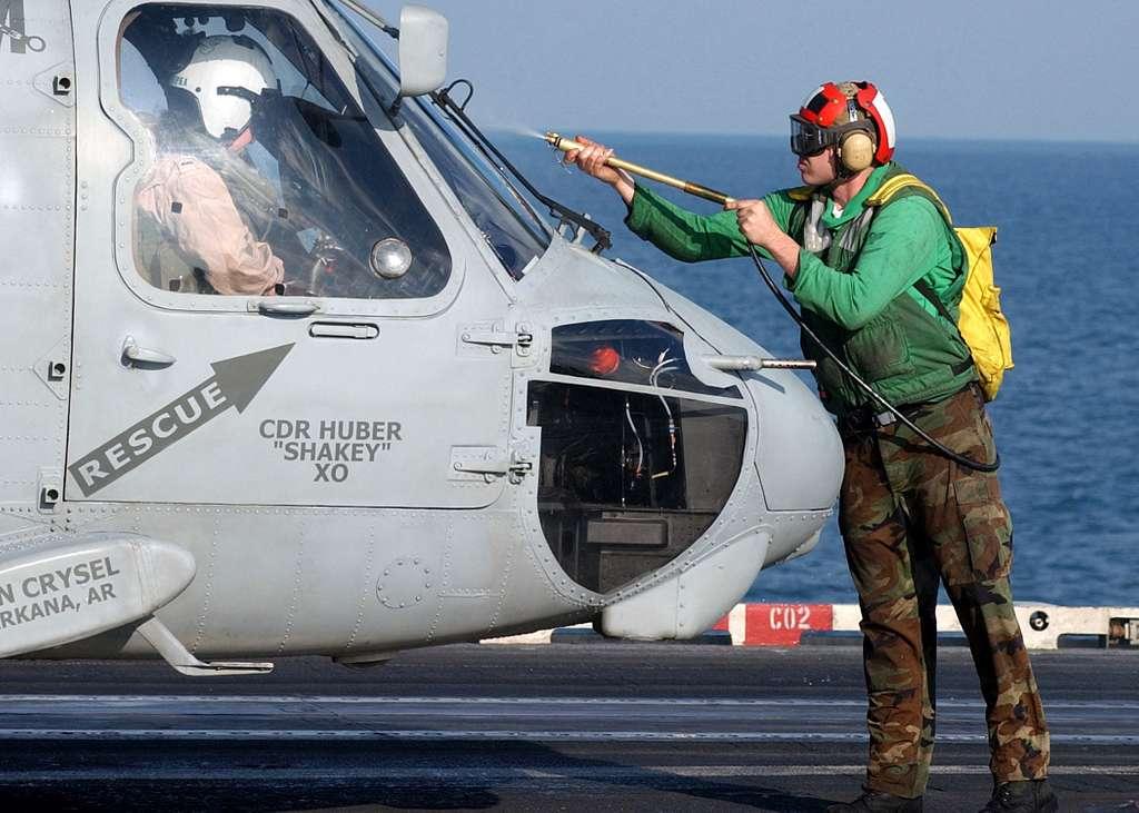 Aviation Electronics Technician 3rd Class Michael Yorkovitch washes the windscreen of an SH-60F Seahawk before flight.