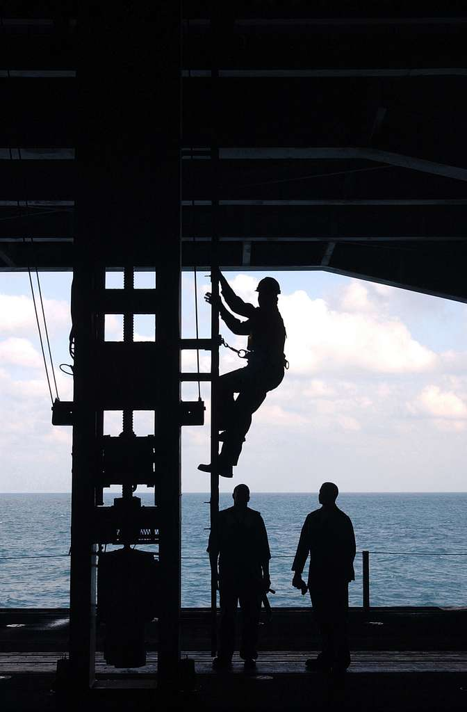 Fireman Marcus Ross lubricates a sliding payeye kingpost used for cargo transfers during underway replenishments.