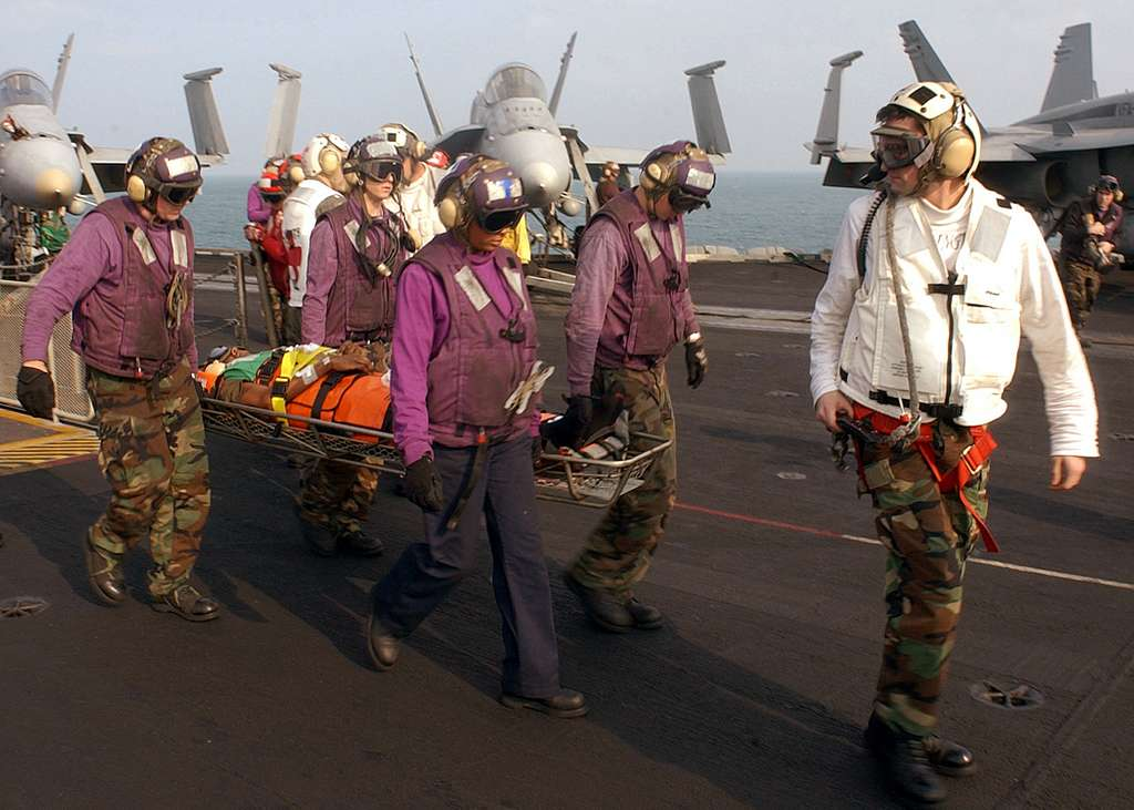 Sailors help carry an injured shipmate to an MH-53E Sea Dragon assigned to the Blackhawks of Helicopter Mine Countermeasures One Five (HM-15) aboard the Nimitz-class aircraft carrier USS Harry S. Truman (CVN 75).